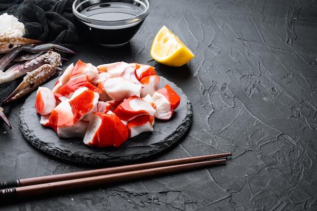 Ensemble de surimi asiatique, sur planche de pierre, sur fond noir, avec fond et espace pour le texte
