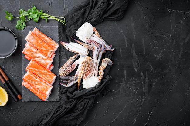 Ensemble de surimi asiatique, sur planche de pierre, sur fond noir, vue de dessus à plat, avec fond et espace pour le texte