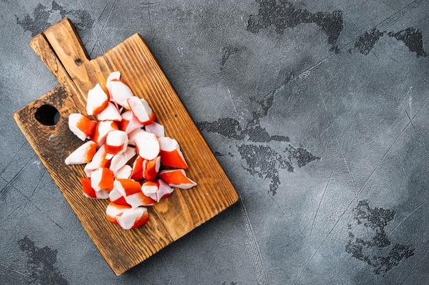 Ensemble de surimi de collation asiatique, sur une planche à découper en bois, sur fond gris, vue de dessus à plat, avec fond et espace pour le texte