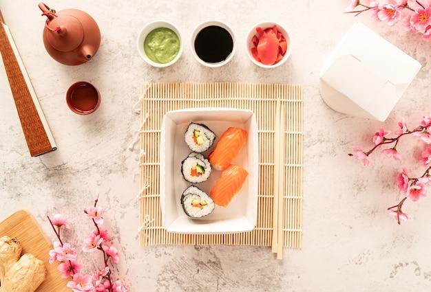 Ensemble de sushi dans une boîte en papier kraft jetable avec souce de soja, gingembre et wasabi