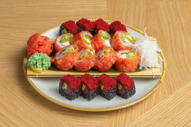 Ensemble de sushi de différents rouleaux avec thon, saumon, crevettes, œufs de poisson volant tobiko, gingembre, radis daikon, riz noir avec seiche et cherinles au wasabi.