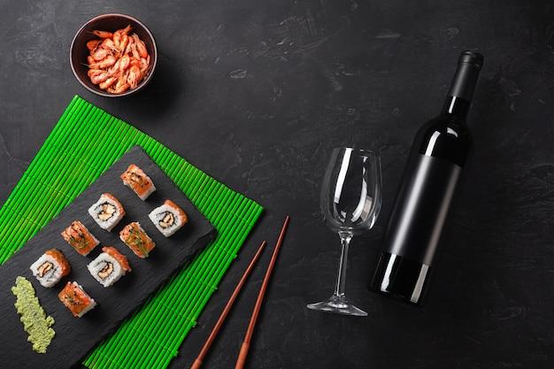 Ensemble de sushi et maki avec une bouteille de vin sur la table en pierre. vue de dessus avec espace de copie