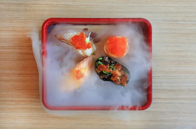 Ensemble de sushi nami servi avec du froid fumé sur une table en bois. cuisine japonaise traditionnelle.