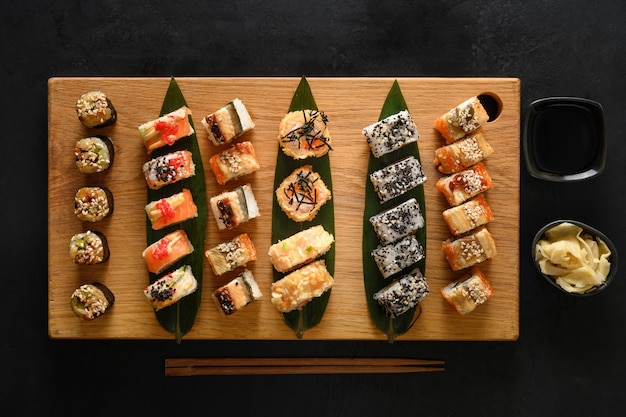 Ensemble de sushi servi sur une planche à découper en bois sur une surface noire. vue d'en-haut. style plat.