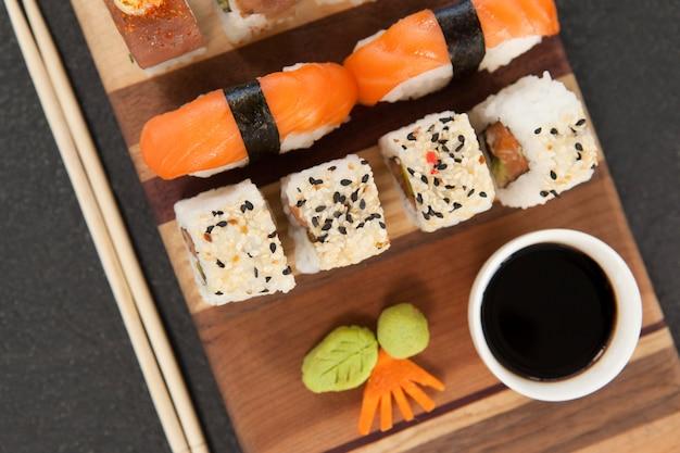 Ensemble de sushis assortis servi avec des baguettes et de la sauce soja sur planche de bois