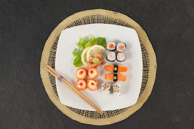 Ensemble de sushis assortis servi avec des baguettes sur un tapis de sushi