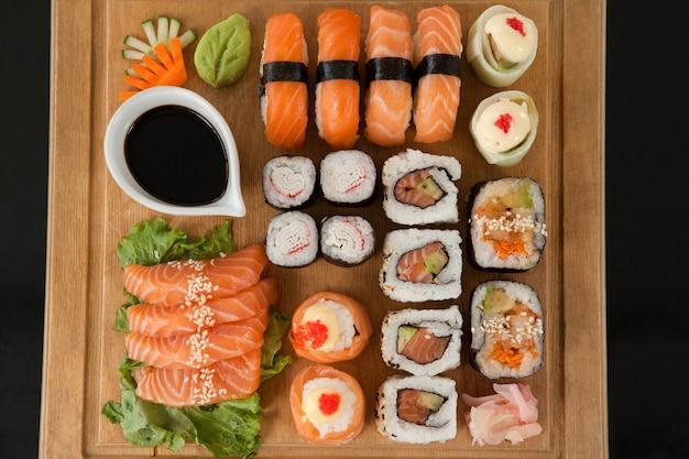 Ensemble de sushis assortis servi sur un plateau en bois sur fond noir