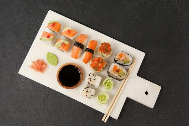 Ensemble de sushis assortis servi avec sauce soja et baguettes sur tableau blanc