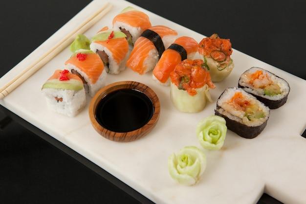 Ensemble de sushis assortis servi avec sauce soja sur tableau blanc