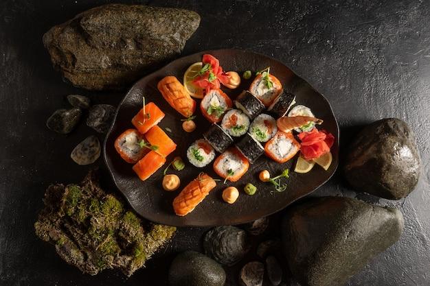 Un ensemble de sushis sur une belle assiette noire. plat japonais de sashimi, petits pains, makis.