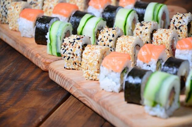 Un ensemble de sushis composé de plusieurs rouleaux est situé sur une découpe en bois