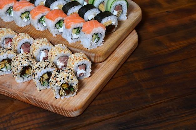 Ensemble de sushis composé de plusieurs rouleaux situé sur une planche à découper en bois sur une table de la cuisine