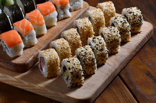 Ensemble de sushis composé de plusieurs rouleaux situé sur une planche à découper en bois sur une table