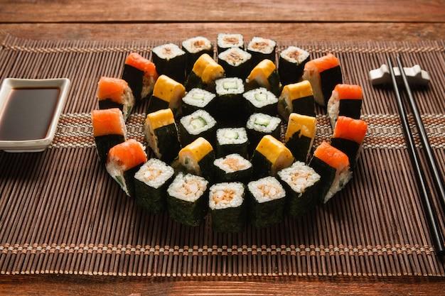 Ensemble de sushis japonais colorés et lumineux, ornement rond de rouleaux de maki servis sur un tapis de paille marron, en gros plan. art culinaire japonais, cuisine nationale, photo du menu du restaurant.