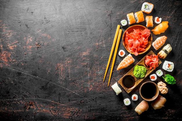 Ensemble de sushis japonais traditionnels et petits pains au gingembre mariné et sauce soja. sur une surface rustique sombre