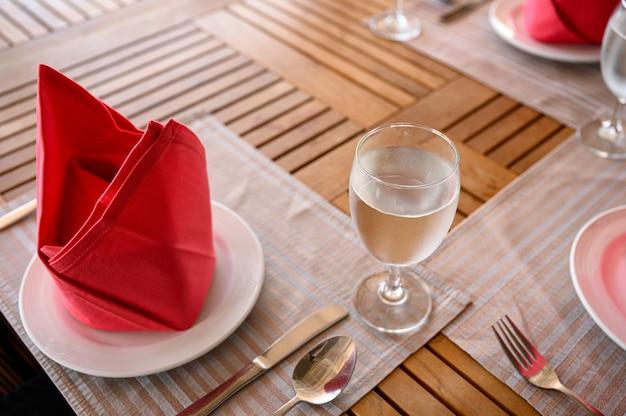 Ensemble de table en bois avec vaisselle en céramique, ustensile en argent, serviette de table rouge et eau
