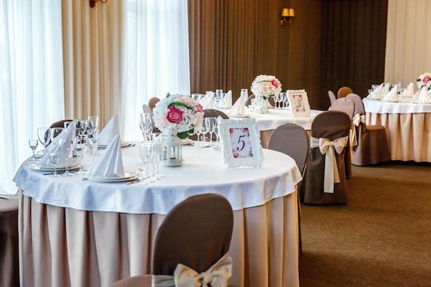 Ensemble de table fantaisie pour le dîner avec composition florale au restaurant, arrière-plan intérieur de luxe. décoration de banquet élégante de mariage et articles pour la nourriture organisés par le service de restauration sur table blanche.