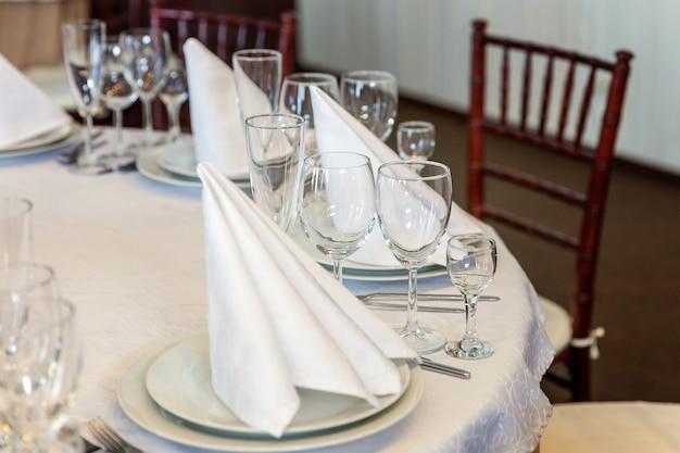 Ensemble de table de fantaisie pour le dîner avec des verres de serviette au restaurant, arrière-plan intérieur de luxe. décoration de banquet élégante de mariage et articles pour la nourriture organisés par le service de restauration sur une table en nappe blanche.