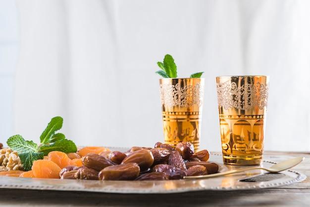 Ensemble de tasses avec des brindilles de plantes et de fruits secs sur un plateau sur la table