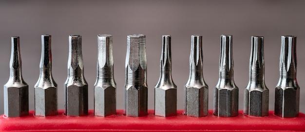 Ensemble de têtes pour tournevis, collection d'outils sur table rouge.