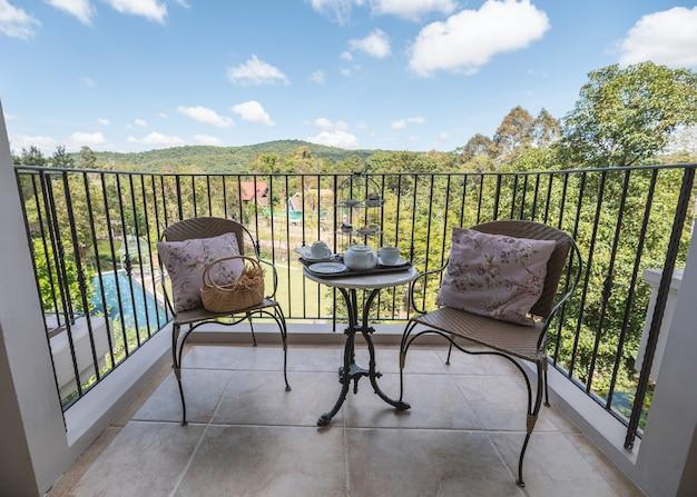 Ensemble de thé de l'après-midi avec dessert et oreiller sur des chaises tissées sur balcon en vacances