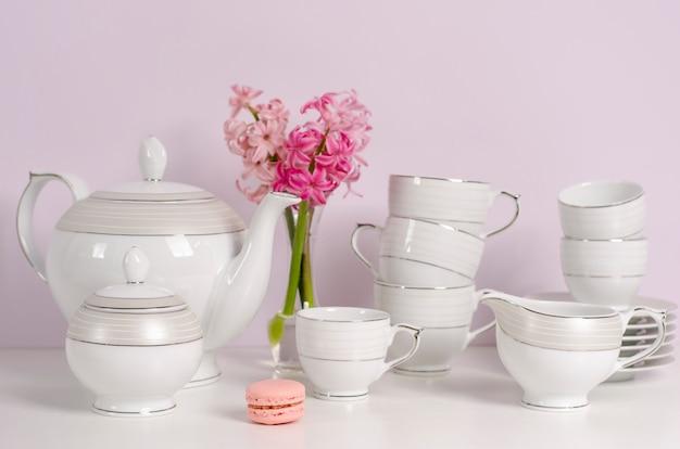 Ensemble de thé et café en macaron et porcelaine ou vaisselle à fleurs roses sur table blanche