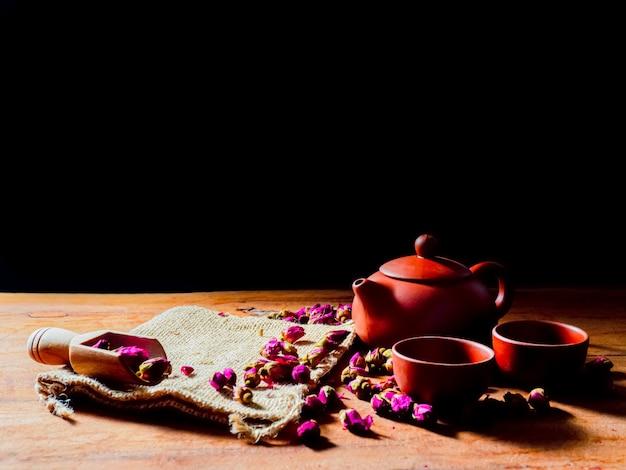 Ensemble de théière et tasse de thé avec des feuilles de thé rose sur table en bois et fond noir