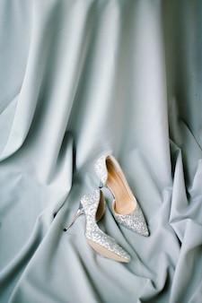 Ensemble de tissu gris et talons et décoration de mariage sur fond texturé gris. vue de dessus.