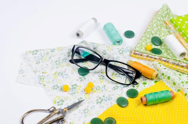 Ensemble de tissus colorés jaunes et verts, ciseaux, boutons, bobines de fil et verres
