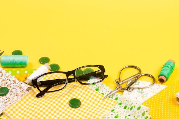 Ensemble de tissus jaunes et verts, ciseaux, boutons, bobines de fil et verres sur jaune