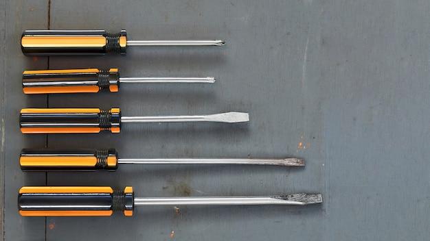 Un ensemble de tournevis différents sur un fond en bois gris
