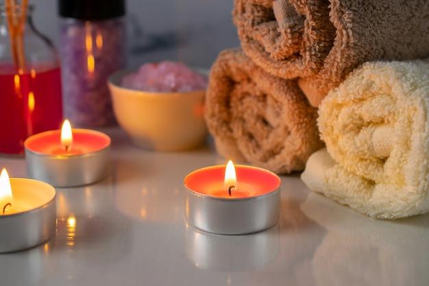 Ensemble de traitement spa avec du sel parfumé, des bougies, des serviettes et de l'huile aromatique