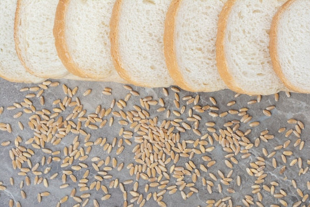 Ensemble de tranches de pain grillé avec des grains d'avoine sur fond de marbre.