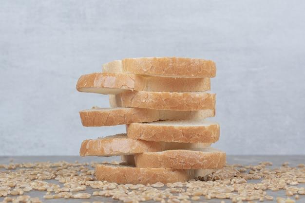 Ensemble de tranches de pain grillé avec des grains d'avoine sur une surface en marbre