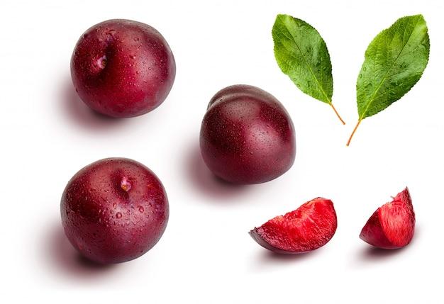 Ensemble et tranches de prunes sur fond blanc