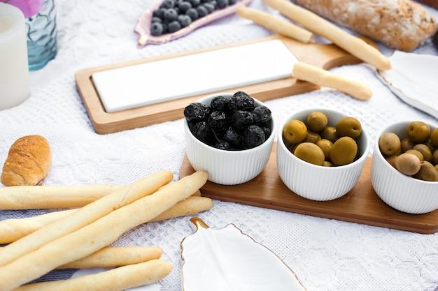 Ensemble de trois bols blancs aux olives sur un plateau en bois sur une couverture blanche