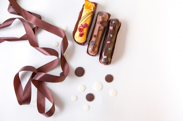 Un ensemble de trois éclairs avec différentes garnitures et design isoler sur une surface blanche décorée avec des gouttes de chocolat et un ruban de soie brune