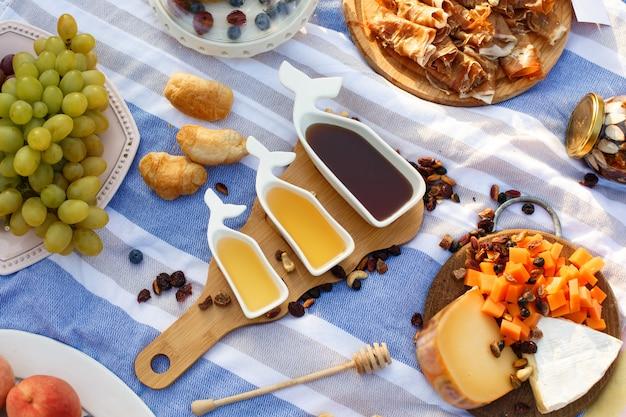 Ensemble de trois saucières blanches avec du miel sucré sur un plateau en bois au pique-nique