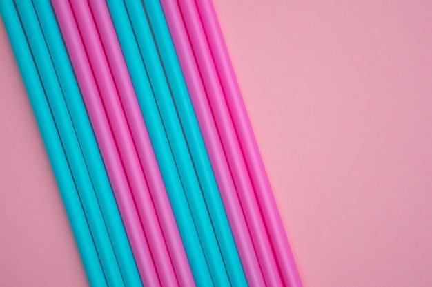 Ensemble de tubes à cocktail biodégradables bleus et roses sur fond de papier rose.