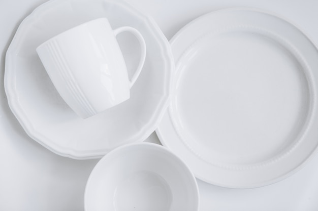 Ensemble d'ustensiles blancs de trois assiettes différentes et une tasse dans une assiette