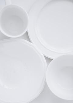 Ensemble d'ustensiles blancs de trois assiettes différentes et une tasse sur un fond blanc