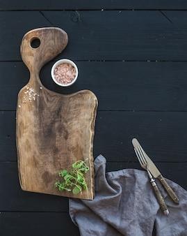 Ensemble d'ustensiles de cuisine. ancienne planche à découper rustique en bois de noyer, sel et herbe d'origan