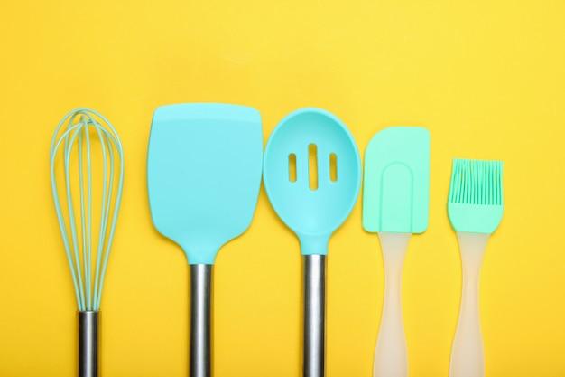 Ensemble d'ustensiles de cuisine: pinceau culinaire et fouet, spatule sur jaune. vue de dessus