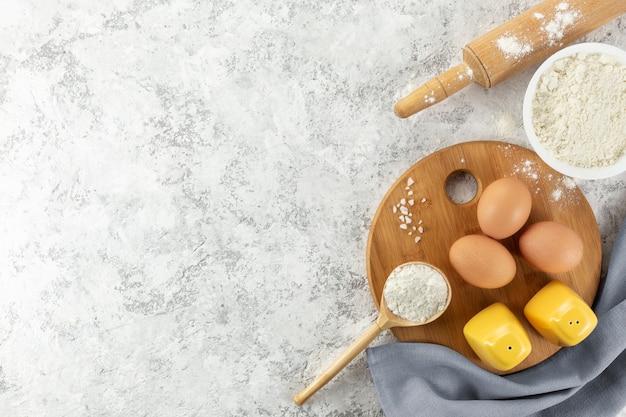 Ensemble d'ustensiles de cuisine avec des produits sur fond blanc.