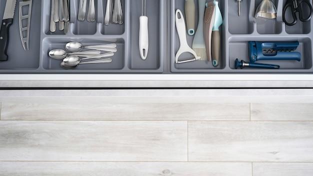 Ensemble d'ustensiles de cuisine propres dans le tiroir, place pour le texte. mise à plat.