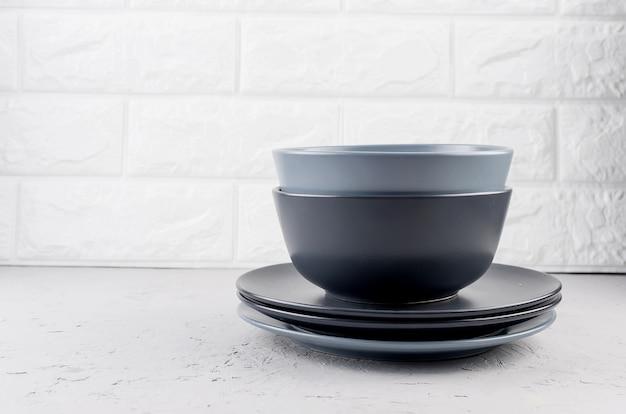 Ensemble de vaisselle en céramique propre sur fond de béton gris, concept de jeu de vaisselle