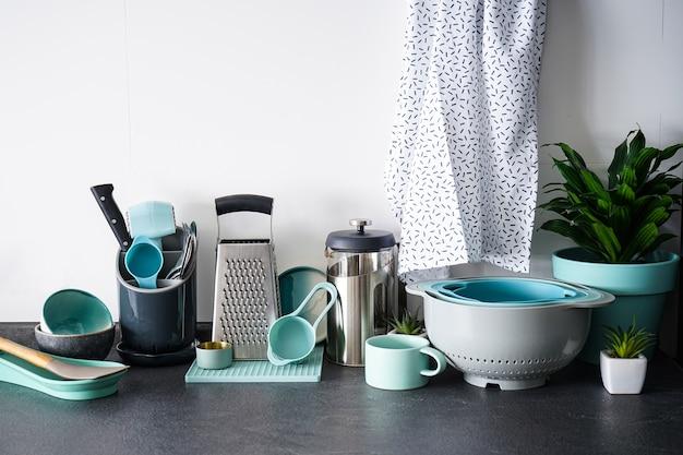 Ensemble de vaisselle et ustensiles de cuisine sur un mur blanc.