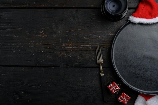 Ensemble de vaisselle vide de noël, vue de dessus à plat, avec espace de copie pour le texte ou la nourriture, sur fond de table en bois noir