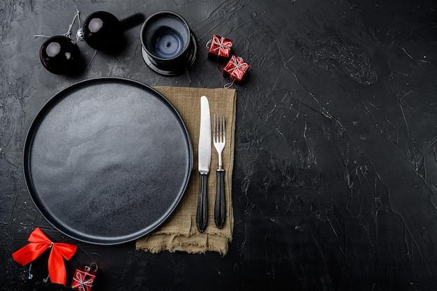 Ensemble de vaisselle vide de noël, vue de dessus à plat, avec espace de copie pour le texte ou la nourriture, sur fond de table en pierre noire noire