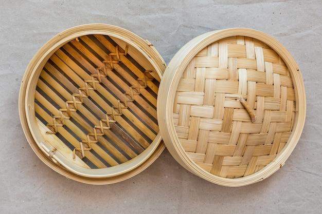 Ensemble vapeur en bambou, ustensiles de cuisine chinois sur papier gris.